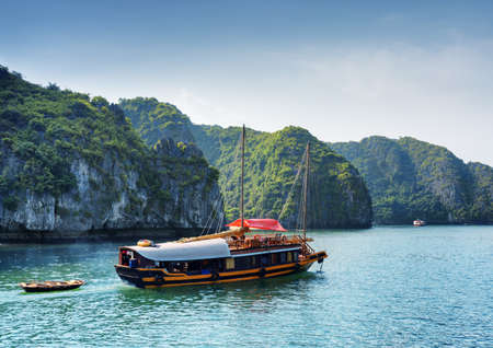 the bay: Tourist boat in the Ha Long Bay at the Gulf of Tonkin of the South China Sea, Vietnam. Beautiful landscape formed by karst isles. The Halong Bay is a popular tourist destination of Asia. Stock Photo