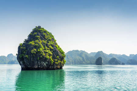halong: Beautiful karst isle on blue sky background in the Ha Long Bay (Descending Dragon Bay) at the Gulf of Tonkin of the South China Sea, Vietnam. The Halong Bay is a popular tourist destination of Asia.