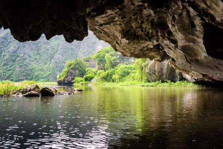 ngo: Scenic view of the Ngo Dong River from natural karst grotto. The Tam Coc portion, Ninh Binh Province, Vietnam. The river flows through cave. The Tam Coc is a popular tourist attraction in Vietnam.