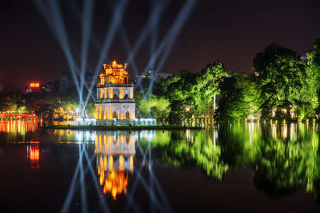 Night view of the Turtle Tower among blue light rays in middle of the Hoan Kiem Lake (Lake of the Returned Sword) at historic centre of Hanoi in Vietnam. The Huc Bridge is visible in background.