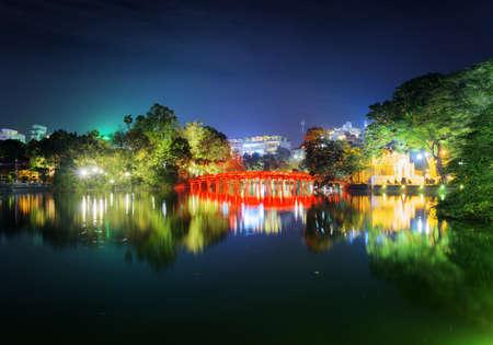 returned: Night view of the Huc Bridge (Morning Sunlight Bridge) on the Hoan Kiem Lake (Lake of the Returned Sword) in historic centre of Hanoi, Vietnam. The bridge reflected in the lake.