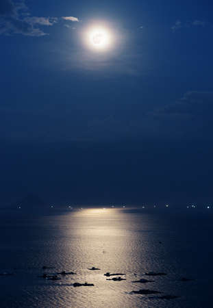 moonlight: Full moon reflected in water of Nha Trang Bay of South China Sea in Vietnam at night. Marine farms illuminated by beautiful mysterious moonlight. Island and lights of ships are visible in background. Stock Photo