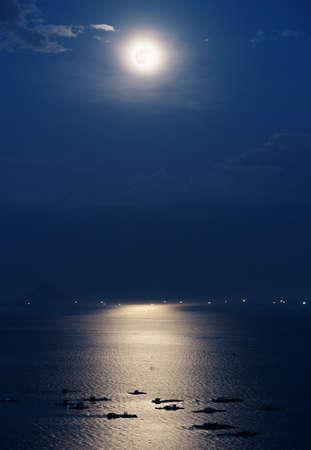 luz de luna: luna llena reflejada en el agua de la bahía de Nha Trang del Mar Meridional de China en Vietnam por la noche. granjas marinas iluminadas por la luz de la luna hermosa misteriosa. Isla y las luces de los barcos son visibles en el fondo. Foto de archivo