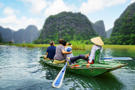 propel: Tourists traveling in boat along the Ngo Dong River and taking selfie at the Tam Coc, Ninh Binh Province, Vietnam. Rower using her feet to propel oars. Landscape formed by karst towers and rice fields
