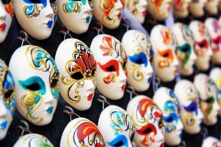 painted face mask: VENICE, ITALY - AUGUST 24, 2014: Side view of authentic and original Venetian full-face masks for Carnival in street shop of Venice, Italy. Handmade masks with ornate design and bright colors.