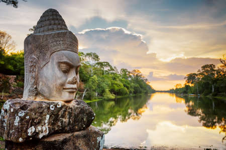 Stone face Asura on causeway near South Gate of Angkor Thom in Siem Reap, Cambodia. Beautiful sunset over ancient moat in background. Mysterious Angkor Thom is a popular tourist attraction. Stock Photo