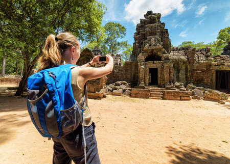 take a history: Young female tourist with blue backpack and smartphone taking picture of the gopura among mysterious ruins of ancient Preah Khan temple in Angkor. Siem Reap, Cambodia.
