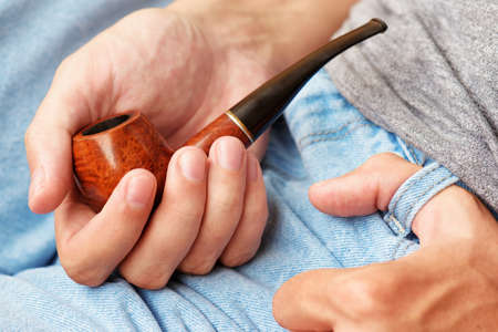 denim shorts: Young man holding smoking pipe in hand. Closeup view. Blue denim shorts in background. Stock Photo
