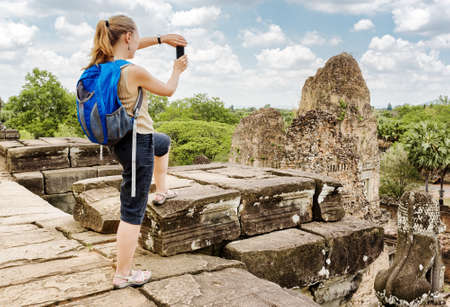 take a history: Young female tourist with backpack taking picture with smartphone from the top of ancient Pre Rup temple in Angkor on blue sky background. Siem Reap, Cambodia.