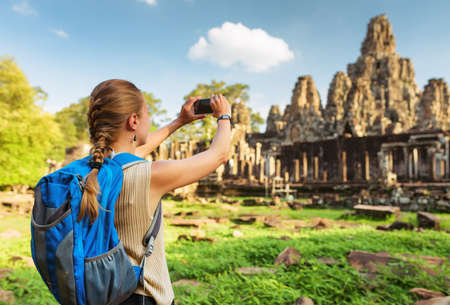 siem reap: Young female tourist with blue backpack and smartphone taking picture of ancient Bayon temple in Angkor Thom on blue sky background in evening sun. Siem Reap, Cambodia.