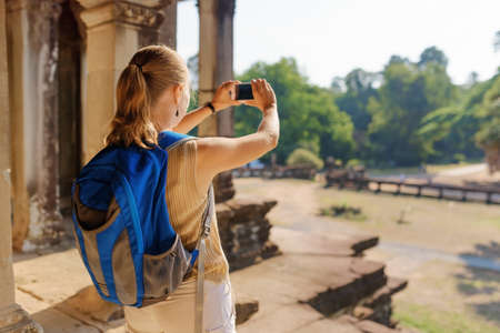 take a history: Young female tourist with blue backpack and smartphone taking picture among mysterious ruins of ancient temple complex Angkor Wat in Siem Reap, Cambodia.