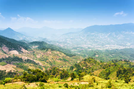 lat: Beautiful view of the valley in the mountains on the Langbian Plateau around Da Lat city (Dalat) on the blue sky background in Vietnam. Da Lat is a popular tourist destination of Asia.