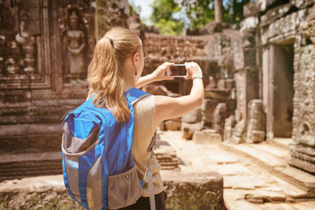 take a history: Closeup view of young female tourist with blue backpack and smartphone taking picture among mysterious ruins of ancient Preah Khan temple in Angkor. Siem Reap, Cambodia. Toned image.