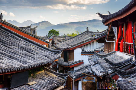 Scenic view of traditional Chinese tile roofs of houses in the Old Town of Lijiang, Yunnan province, China. Mountains in background. The Old Town of Lijiang is a popular tourist destination of Asia.