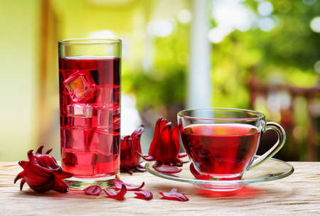 Cup of hot hibiscus tea (rosella, karkade, red sorrel) and the same cold drink with ice cubes in glass on wooden table at terrace. Drink made from magenta calyces (sepals) of roselle flowers.
