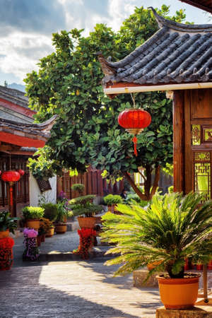 destination scenic: Scenic view of traditional Chinese wooden houses decorated with red lanterns on narrow street in the Old Town of Lijiang, Yunnan province, China. Lijiang is a popular tourist destination of Asia. Stock Photo
