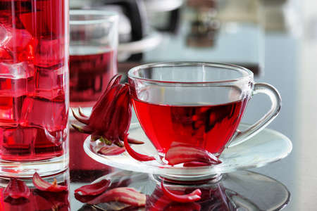 hot drink: Cup of hot hibiscus tea (rosella, karkade, red sorrel, Agua de flor de Jamaica) on kitchen table. The same drink with ice cubes in glass. Drink made from magenta calyces (sepals) of roselle flowers. Stock Photo