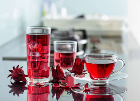 hibiscus flowers: Cup of hot hibiscus tea (karkade, red sorrel, Agua de flor de Jamaica) and the same cold drink with ice in glass on kitchen table. Drink made from magenta calyces (sepals) of roselle flowers. Stock Photo
