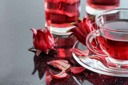 Closeup view of cup of hibiscus tea (rosella, karkade, red sorrel) on table. Drink made from magenta calyces (sepals) of roselle flowers. Healthy herbal tea rich in vitamin C and minerals. Stock Photo