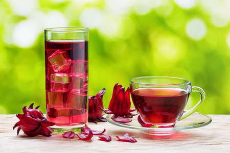 Tasse heißen Tee Hibiskus (karkade, rot Sauerampfer, Agua de flor de Jamaika) und das gleichen kalten Getränk mit Eiswürfeln im Glas auf der Natur Hintergrund. Magenta-Farbe Kelche (Kelchblätter) von Roselle Blumen auf dem Tisch.