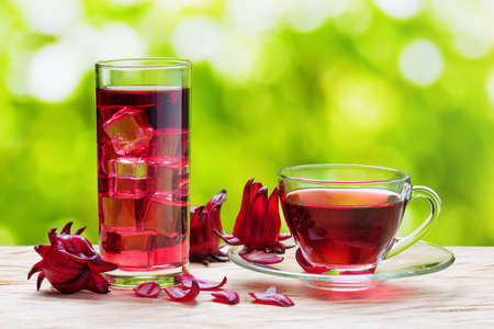 Cup of hot hibiscus tea (karkade, red sorrel, Agua de flor de Jamaica) and the same cold drink with ice cubes in glass on nature background. Magenta-color calyces (sepals) of roselle flowers on table.