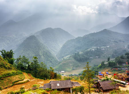 lien: Rice terraces and village at highlands of Sapa District, Lao Cai Province, Vietnam. Rays of sunlight through clouds in the Hoang Lien Mountains are visible in background.