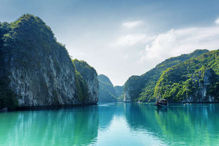 blue dragon: Beautiful view of lagoon in the Halong Bay (Descending Dragon Bay) at the Gulf of Tonkin of the South China Sea, Vietnam. Landscape formed by karst towers-isles on blue sky background.