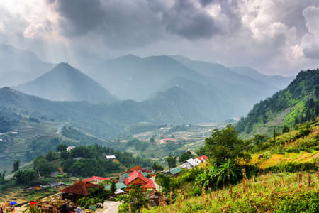 Scenic view of Cat Cat Village at highlands of Sapa District, Lao Cai Province, Vietnam. Stormy dramatic cloudy sky and the Hoang Lien Mountains are visible in background.