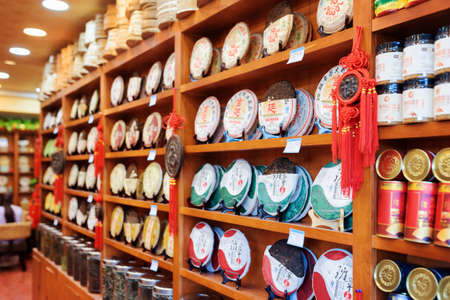 pu: LIJIANG, YUNNAN PROVINCE, CHINA - OCTOBER 23, 2015: Wide range of traditional Chinese tea on wooden shelves at tea shop in the Old Town of Lijiang. Disks of Yunnan Puer. Shallow depth of field.