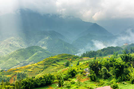 lien: Scenic view of rice terraces at highlands and rays of sunlight through storm clouds in the Hoang Lien Mountains of Sapa District, Lao Cai Province, Vietnam. Sa Pa is a popular tourist destination. Stock Photo