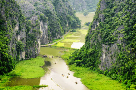 Top view of the Ngo Dong River and boats at the Tam Coc portion, Ninh Binh Province, Vietnam. Landscape formed by karst towers and rice fields. The Tam Coc is a popular tourist attraction in Vietnam.