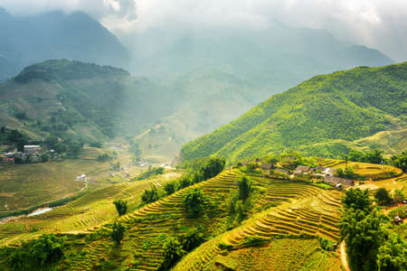 lien: Amazing view of rays of sunlight illuminating green rice terraces through storm clouds at highlands of Sapa District, Lao Cai Province, Vietnam. Sa Pa is a popular tourist destination of Asia. Stock Photo