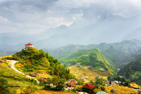 lien: House on mountain top at Sapa District, Lao Cai Province, Vietnam. View of rice terraces and village at highlands. The Hoang Lien Mountains and stormy sky are visible in background.