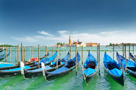 lagoon: A row of gondolas parked beside the Riva degli Schiavoni in Venice, Italy. View of the Venetian Lagoon at summer. The Church of San Giorgio Maggiore on island of the same name is visible in background