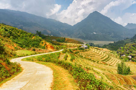 lien: Bending road among rice terraces at highlands of Sapa District, Lao Cai Province, Vietnam. Sa Pa is a popular tourist destination of Asia. The Hoang Lien Mountains are visible in background. Stock Photo