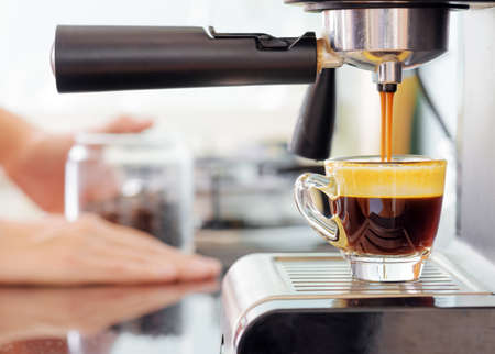espresso cup: Espresso coffee machine in kitchen. Jets of fresh hot invigorating coffee pouring into cup.