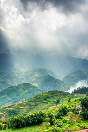 lien: Amazing view of the Hoang Lien Mountains and rays of sunlight through storm clouds. Sapa District, Lao Cai Province, Vietnam. Sa Pa is a popular tourist destination of Asia.