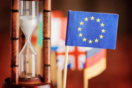 economia: concepto político con la bandera de la Unión Europea. El tiempo se agota. Primer punto de vista de reloj de arena y la bandera de la Unión Europea. Banderas de los países europeos en el fondo.