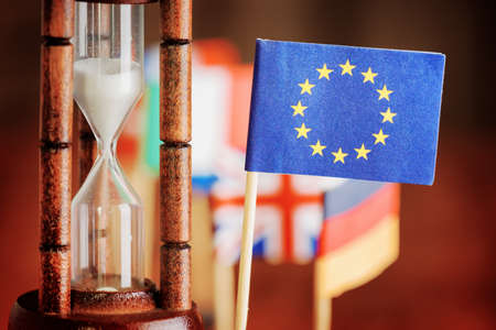 Political concept with flag of the European Union. Time is running out. Closeup view of hourglass and flag of the European Union. Flags of European countries in background.