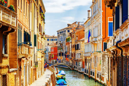 View of the Rio Marin Canal and the Ponte Cappello dei Garzoti from the Ponte de la Bergami in Venice, Italy. Colorful facades of old houses. Venice is a popular tourist destination of Europe.