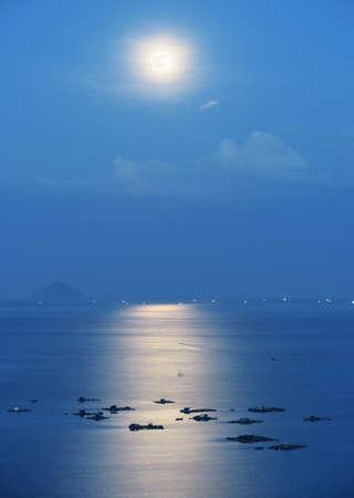 noche y luna: luna llena reflejada en el agua de la bahía de Nha Trang del Mar Meridional de China en Vietnam por la noche. granjas marinas iluminadas por la luz de la luna hermosa misteriosa romántica. Isla es visible en el fondo.