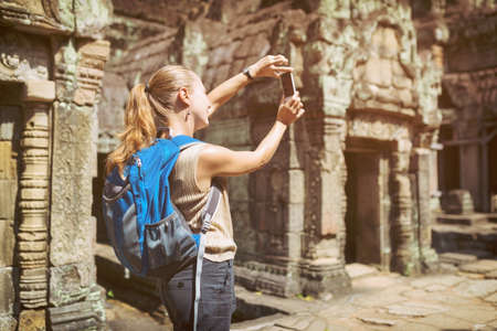 take a history: Young female tourist with blue backpack and smartphone taking picture of mysterious ruins in the ancient Preah Khan temple in Angkor. Siem Reap, Cambodia. Toned image.