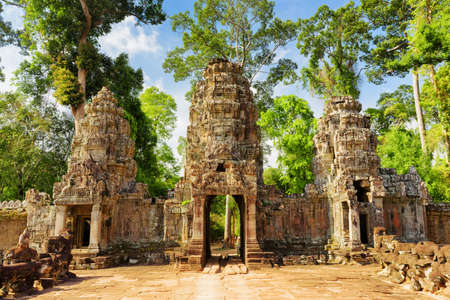 Entrance to ancient Preah Khan temple in Angkor, Siem Reap, Cambodia. Mysterious gopura on woods background. Angkor is a popular tourist attraction. Stock Photo