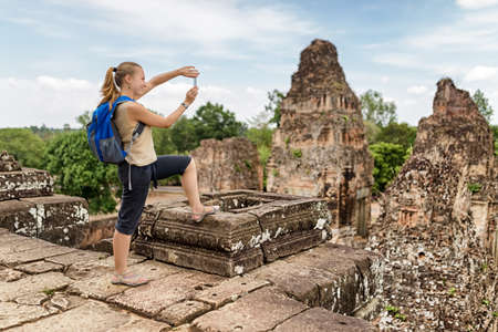 take a history: Young female tourist with blue backpack taking picture with smartphone of mysterious ruins from the top of ancient Pre Rup temple Khmer in Angkor on blue sky background. Siem Reap, Cambodia. Stock Photo