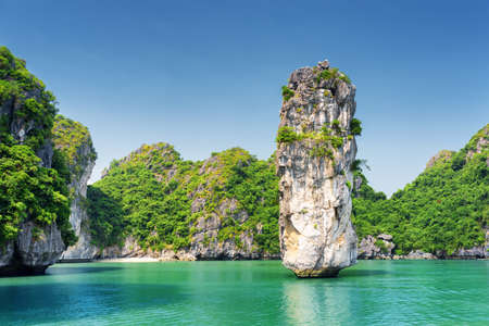 Amazing rock pillar and azure water in the Ha Long Bay (Descending Dragon Bay) at the Gulf of Tonkin of the South China Sea, Vietnam. The Halong Bay is a popular tourist destination of Asia. Stock Photo