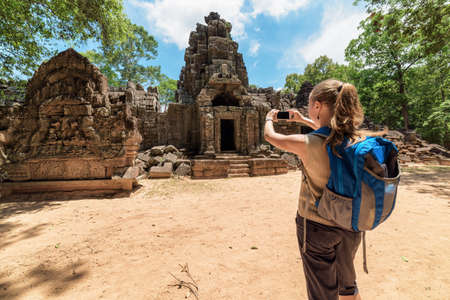 take a history: Young female tourist with blue backpack and smartphone taking picture of the gopura and the bas-relief near the entrance to ancient Preah Khan temple in Angkor. Siem Reap, Cambodia.