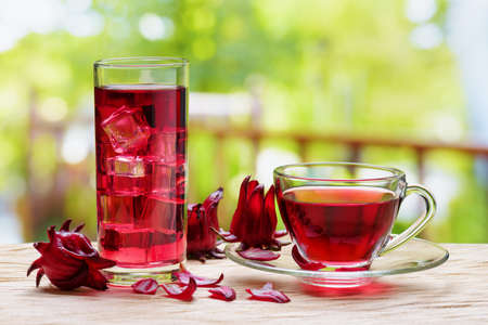 Cup of hot hibiscus tea (karkade, red sorrel, Agua de flor de Jamaica) and the same cold drink with ice cubes in glass on table at terrace. Drink made from magenta calyces (sepals) of roselle flowers.