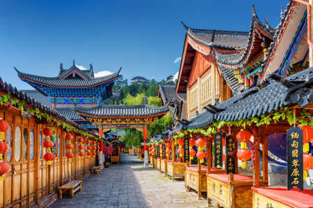 LIJIANG, YUNNAN PROVINCE, CHINA - OCTOBER 23, 2015: Ancient street decorated with traditional Chinese red lanterns in the Old Town of Lijiang. Lijiang is a popular tourist destination of Asia. Zdjęcie Seryjne - 52456510