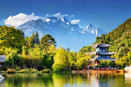 Beautiful view of the Jade Dragon Snow Mountain and the Moon Embracing Pavilion on the Black Dragon Pool in the Jade Spring Park, Lijiang, Yunnan province, China. Stockfoto