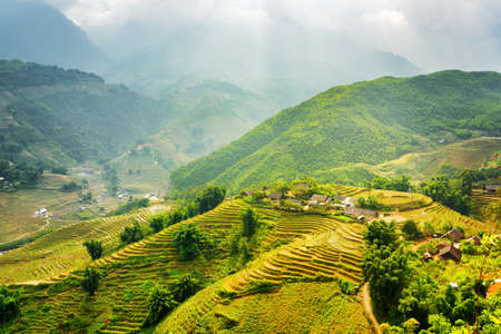 lao: Scenic view of rays of sunlight illuminating green rice terraces through storm clouds at highlands of Sapa District, Lao Cai Province, Vietnam. Sa Pa is a popular tourist destination of Asia. Stock Photo